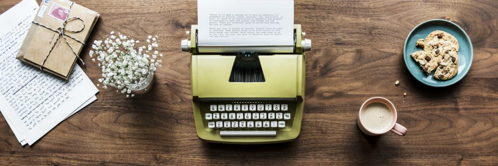 Typewriter on a desk with papers and a cup of coffee and cookies