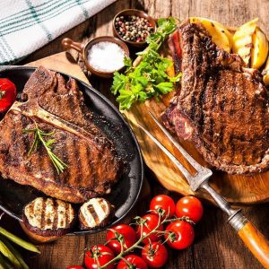two grilled t bone grass fead steaks with vegetables around them