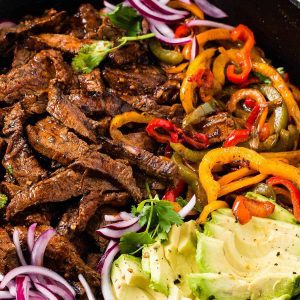 carne asada steak meat with vegetables in a pan