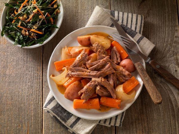 cross rib roast meet that has been shredded and is in a bowl with carrots and potatoes