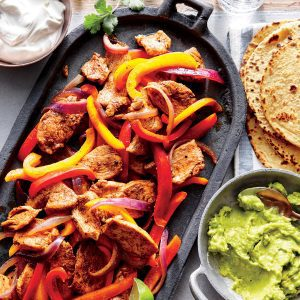 fajita mix on an iron plate with bell peppers and tortillas