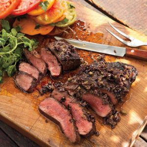 cuts of flat iron steak that have been cooked with vegetables surrounding it