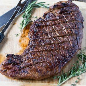 london broil steak on a cutting board parsley