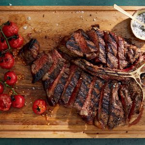 beautifully cooked porterhouse steak that has been cut in to strips