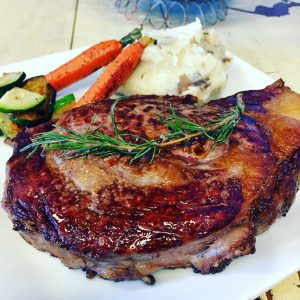 barbecued rib eye steak on a plate with mash potatoes and carrots