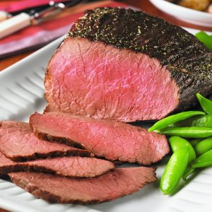 perfectly grilled rump roast that has been sliced on a plate
