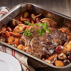 Sirloin tip roast steak in a pan with vegetables surrounding it