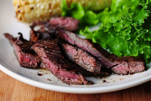 strips of skirt steak on a plate with lettuce