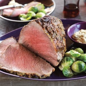 grass fed top round roast on a plate with brussel sprouts