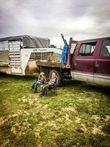 2 kids sitting in chairs on the hipwell ranch property with a truck and trailer in the background